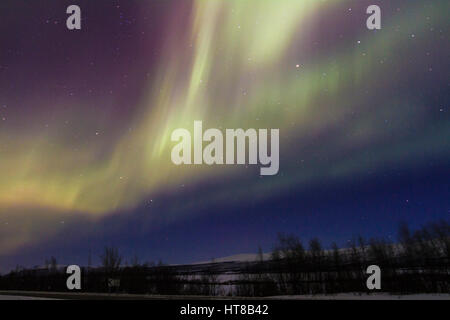Northern light, Aurora borealis, mountains in background, auroa are violett, green, winter season, Kiruna, Swedish - Stock Photo