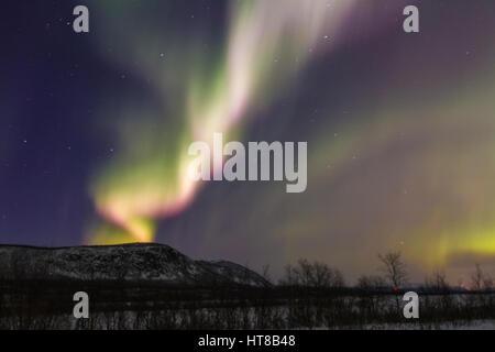 Northern light, Aurora borealis, over Nikkaluokta, mountains in background, auroa are violett, green, winter season, - Stock Photo