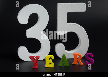 Thirty-five years in large white numerals on a black background. - Stock Photo