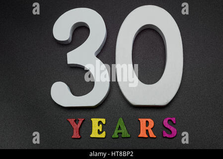Thirty years of large white numerals on a black background. - Stock Photo