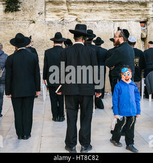 A little boy dressed in a mask next to the Western Wall in Jerusalem, Israel - Stock Photo
