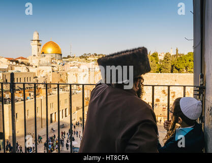 An orthodox Jewish man wearing a shtreimel and a boy overlook the - Stock Photo