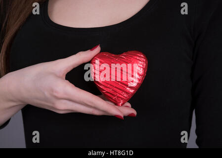 Young woman holding a heart shape chocolate against her chest - Stock Photo