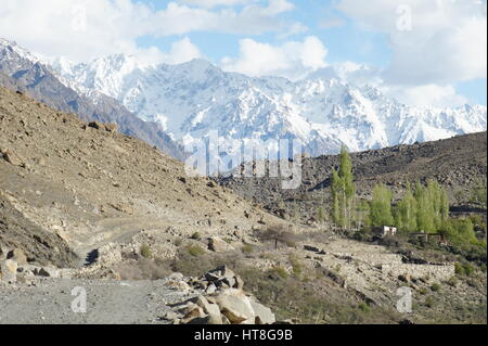 A view of Borit Lake and campsite surrounded by snow covered mountains in Pakistan. - Stock Photo