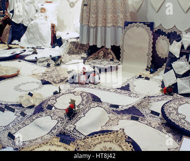 Lace products displayed for sale in a shop window, Bruges, Belgium. - Stock Photo