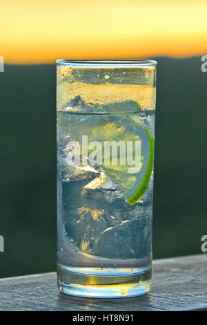 Gin and Tonic in a straight glass with ice and lime or lemon at sunset - Stock Photo