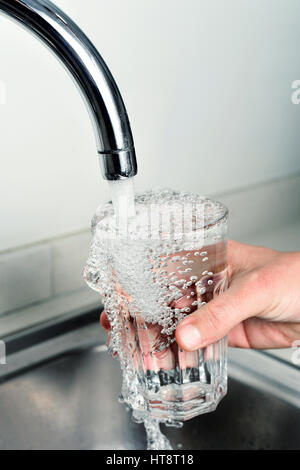 closeup of a young caucasian man filling a glass of tap water - Stock Photo