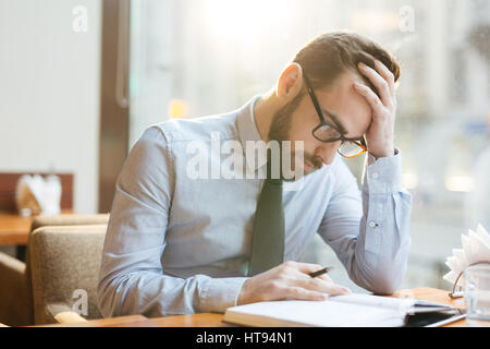 Bearded pensive businessman in shirt and tie sitting in cafe bent over notepad, holding head with his hand and thinking - Stock Photo