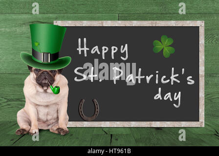 cute pug puppy dog with leprechaun hat for st. patrick's day smoking pipe, sitting next blank chalkboard sign with - Stock Photo