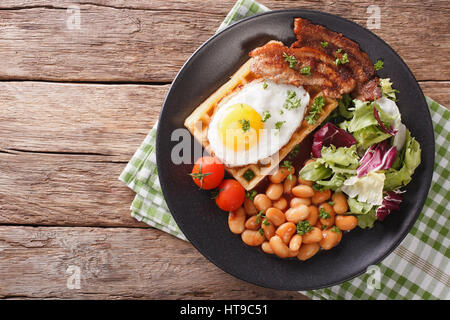 Delicious breakfast: fried egg, waffles, bacon, beans and salad close-up on a plate. horizontal view from above - Stock Photo