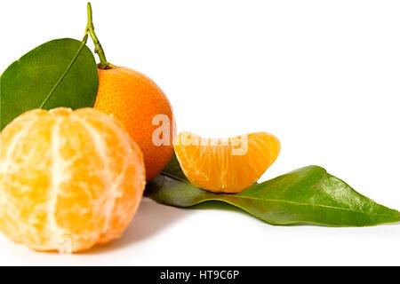 Fresh tangerines and peeled fruit on white background. - Stock Photo