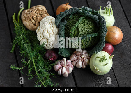 Spring vegetables on a dark background: Savoy cabbage, cauliflower, onion, garlic, kohlrabi, celery root dill. Top - Stock Photo