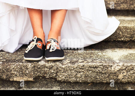 Funny beautiful bride wearing blue running shoes.Close up - Stock Photo