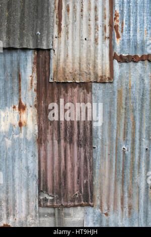 Overlaid sections of rusting galvanised / galvanized steel sheet. Weathered metal texture. - Stock Photo