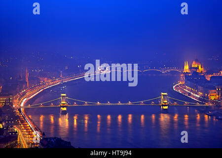 View of  the Széchenyi Chain Bridge and Danube river from Gellert Hill. In the background the Hungarian Parliament. - Stock Photo