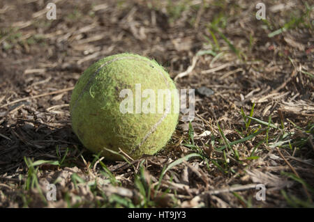 Picture of an old, used tennis ball on the ground surrounded by dirt and grass - Stock Photo