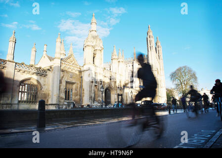 Rush hour in Cambridge in front of Kings College, as bicycle students and commuters cycle along the road, blurred - Stock Photo