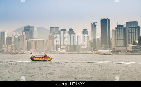 Panorama of a ferry in the Victoria Harbour with the skyscrapers and the Hong Kong skyline. China. - Stock Photo