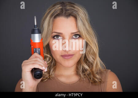 Young woman standing holding an electric screwdriver close to her head. - Stock Photo