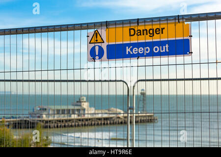 Danger keep out sign on wire barrier at East Cliff following landslip with Bournemouth Pier in the background, Bournemouth, - Stock Photo