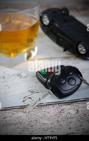 Car keys, glass of whiskey in background. Drinking and driving