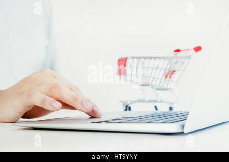 Man using laptop for internet shopping. Bright composition with shopping trolley in background. - Stock Photo