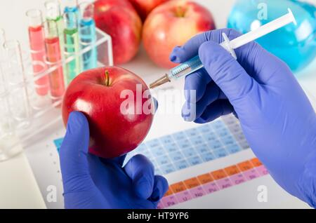 Analyst injects liquid into apple. Genetically modified food in lab concept. - Stock Photo