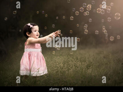 A little girl standing and trying to catch a soap bubble surrounded by lots of bubbles - Stock Photo