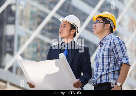 Architect, engineer, project manager or businessman point to building in the city with a blank plan as for construction - Stock Photo