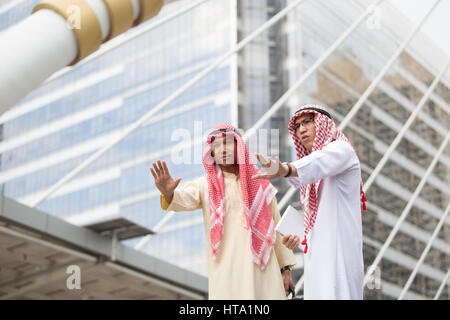 Two Arabian man making a halt gesture with he raised hand indicating a stop (selective focused) - Stock Photo