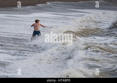 Aberystwyth, Wales, UK. 9th March, 2017. UK Weather: An intrepid young man swimming in the waves in the choppy sea - Stock Photo