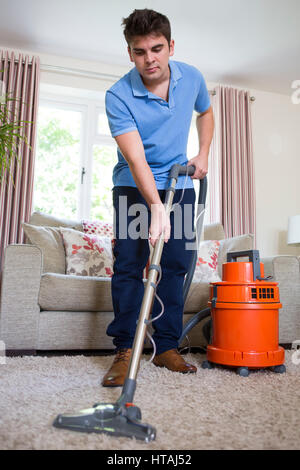 Young Man Professionally Cleaning Carpets - Stock Photo