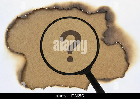Question mark under a magnifier on burnt yellow paper - Stock Photo