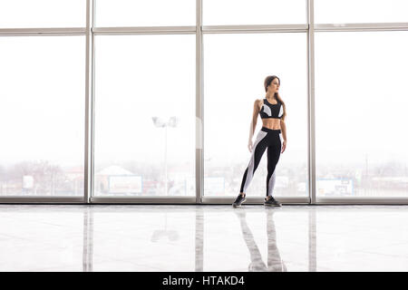 Silhouette of sporty girl before training against panoramic windows - Stock Photo