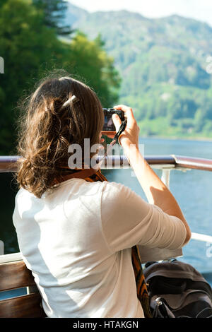 Unrecognisable young female enjoying boat ride, taking photographs, Loch Katrine, Scottish Highlands, UK - Stock Photo