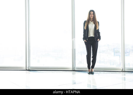 businesswoman standing in office against panoramic windows - Stock Photo
