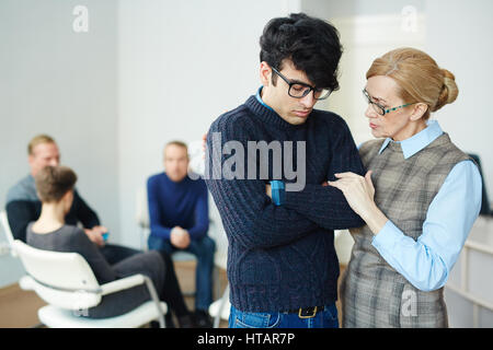 Portrait of mature female psychologist helping young man to overcome his fears and join  group therapy session - Stock Photo