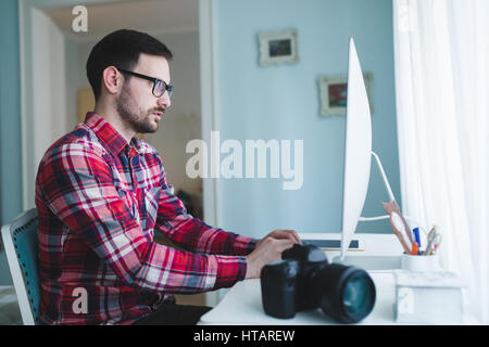 Photographer retoucher working on photos and editing on desktop - Stock Photo