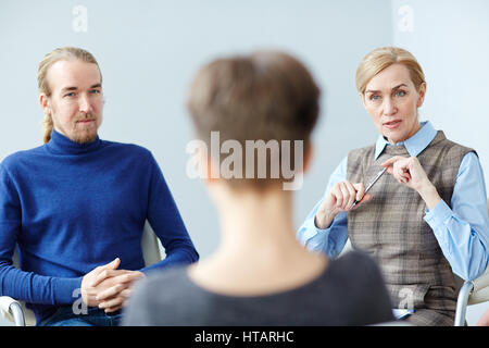 Portrait of mature woman talking to patient in group therapy meeting, consulting about mental health issues - Stock Photo