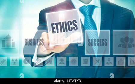 Businessman pressing an Ethics concept button. - Stock Photo