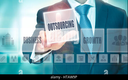 A businessman pressing a Outsourcing button on a transparent screen. - Stock Photo