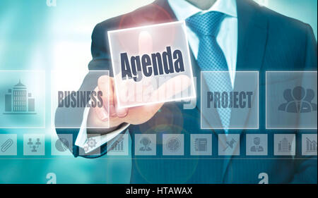 A businessman selecting a Agenda Concept button on a clear screen. - Stock Photo