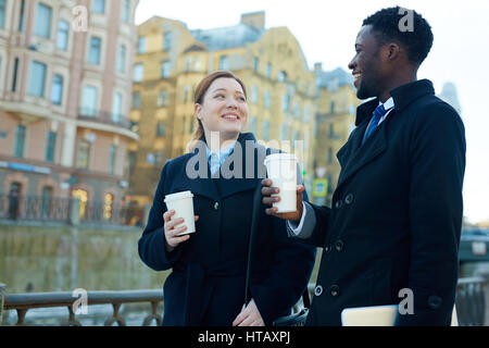 Portrait of two business colleagues leaving office and standing in autumn street by river smiling  and holding disposable - Stock Photo