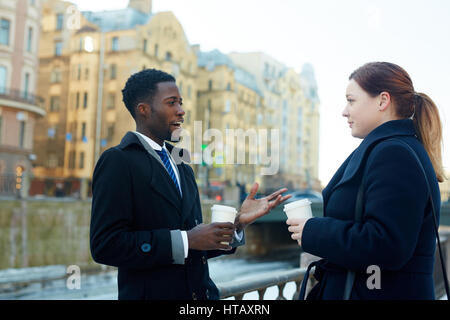 Portrait of two business colleagues leaving office and standing in autumn street by river having conversation and - Stock Photo