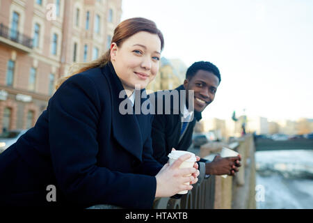 Portrait of two business colleagues leaning on river bank railing and looking at camera, smiling while holding disposable - Stock Photo
