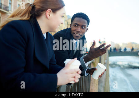 Man and young woman, leaning on river bank railing and talking to each other while holding disposable coffee cups - Stock Photo