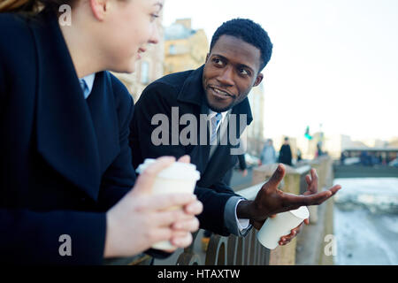 Man and young woman, in street of city, leaning on river bank railing and talking to each other while holding disposable - Stock Photo