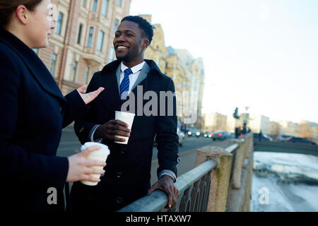 Portrait of two business colleagues in street of city by river talking to each other while holding disposable coffee - Stock Photo