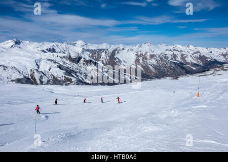 Piste at Meribel, Three Valleys ski resort in the French Alps, on a sunny winters day, with five skiers on the piste - Stock Photo