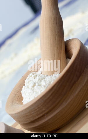 Wheat Flour in a Wooden Mortar with Pestle on a wooden plate - Stock Photo